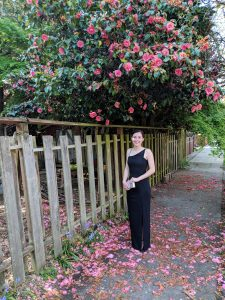 black beaded gown, silver clutch, pink rose bushes