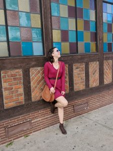 girl in a red dress leaning against a colorful wall