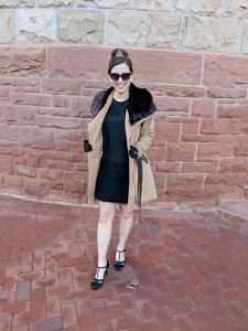 Girl wearing sunglasses and a long camel coat