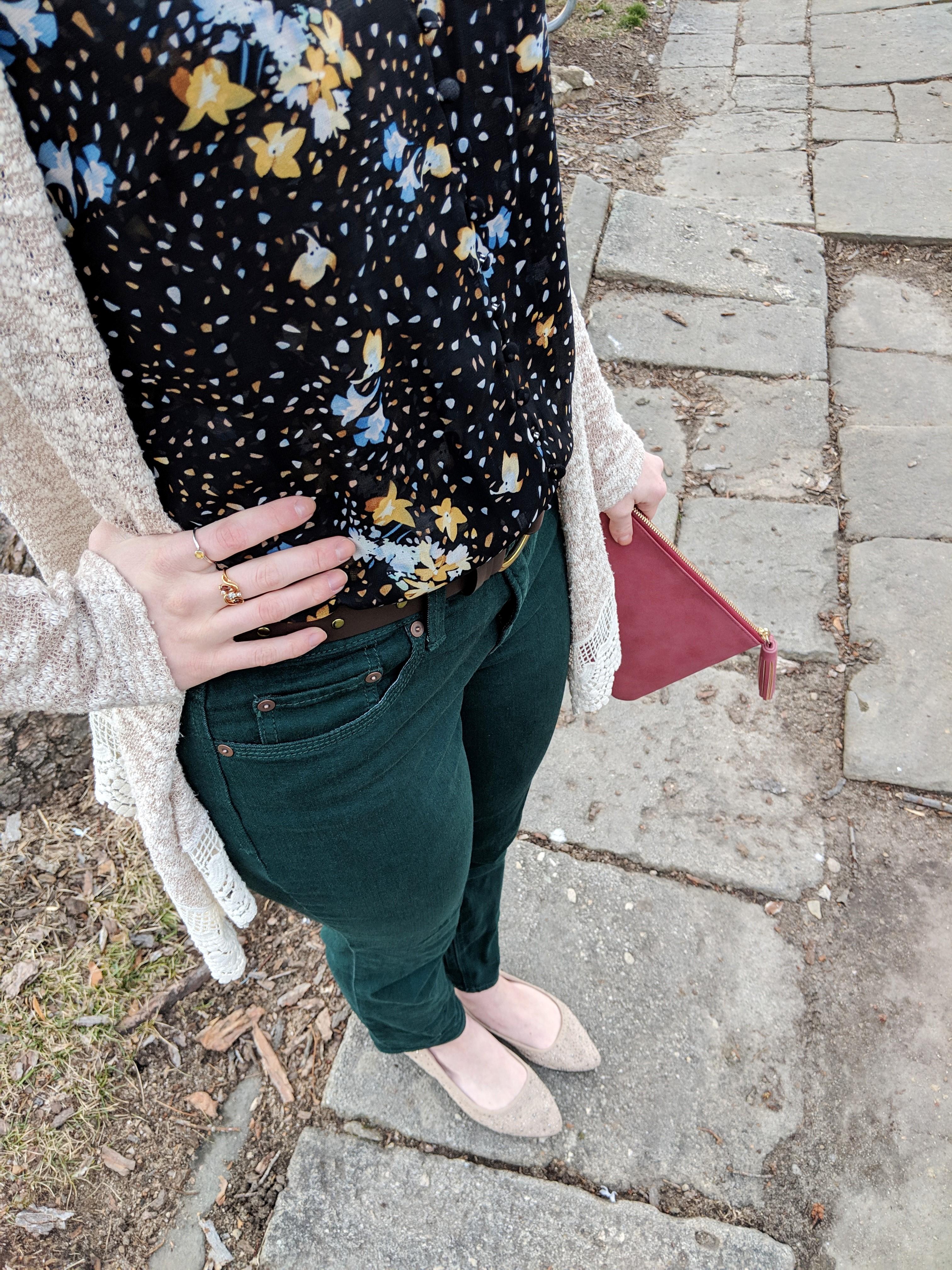black floral Cabi tank top and green jeans