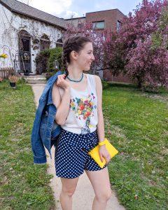 floral graphic tee, polka dot shorts, yellow purse, jean jacket